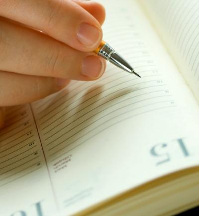 Businesswoman writing in personal organizer
